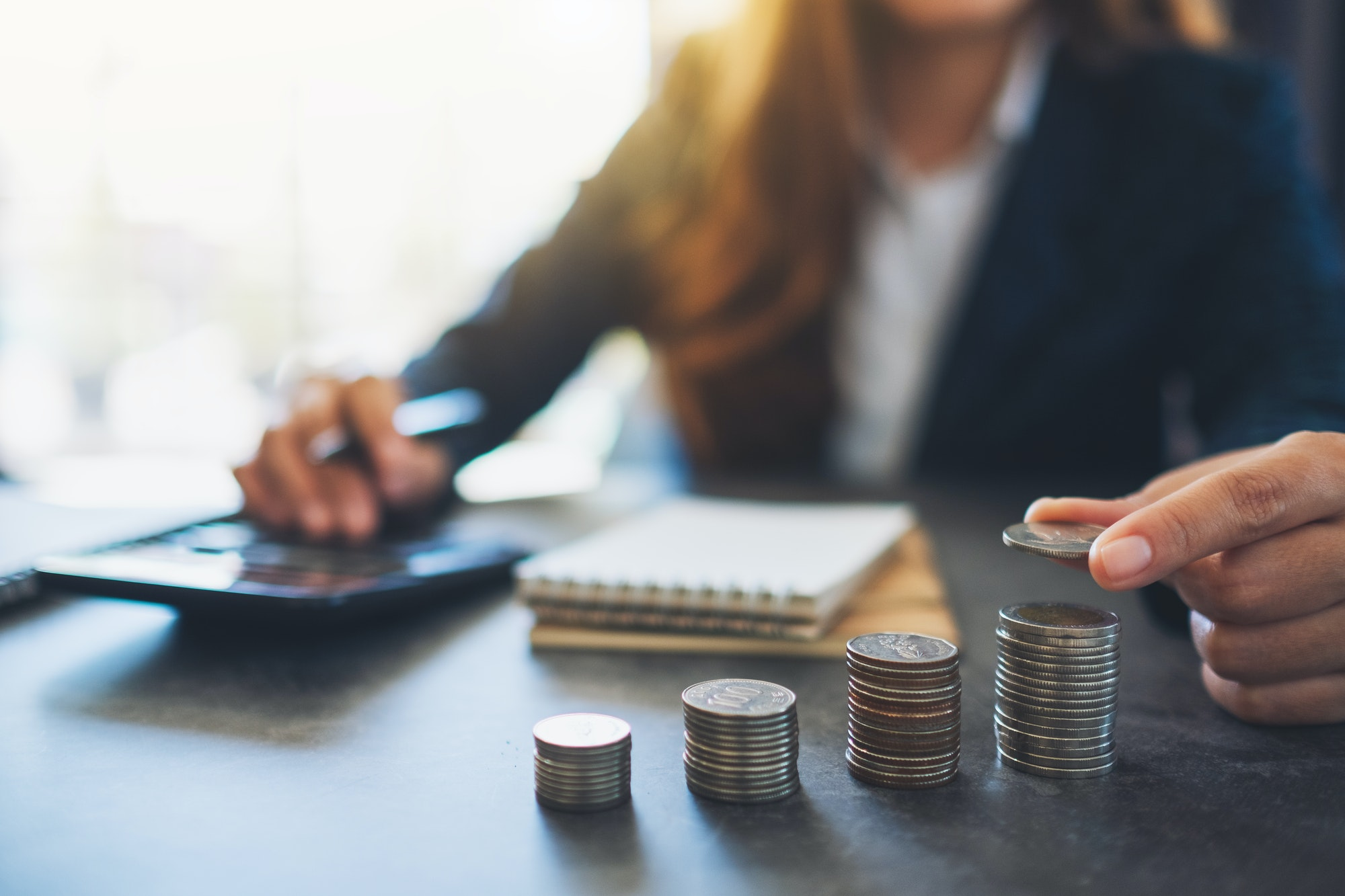 Businesswoman holding and stacking coins while calculating money on the table